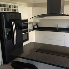 Black and white kitchen with black fridge