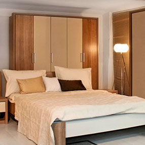 Cream and brown bed with large wardrobes
