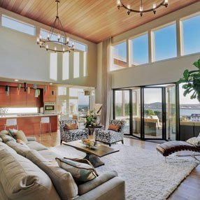 Open plan living room with large bay windows and folding doors